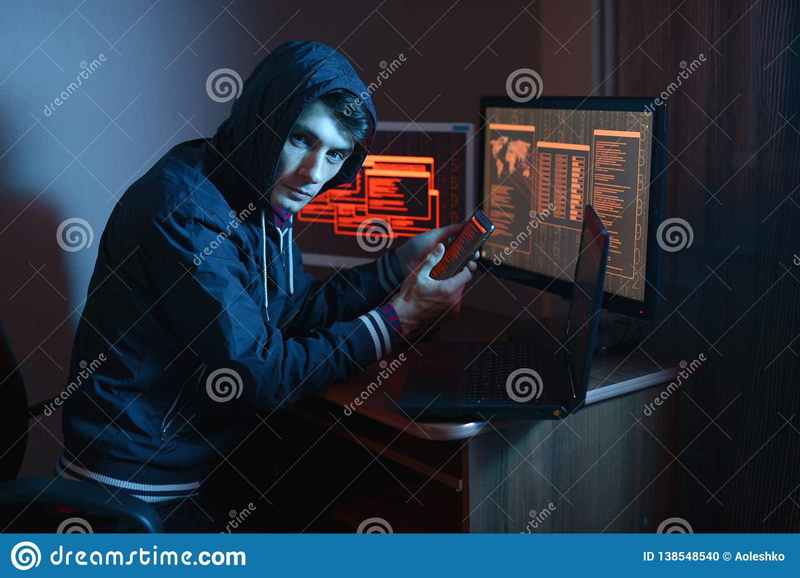 Hacker In The Hood Holding The Phone In His Hands Trying To Hack The