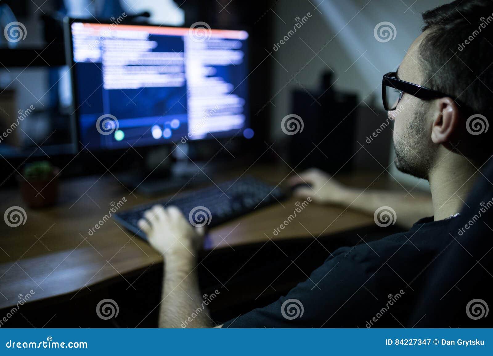 Hacker w słuchawki i eyeglasses z klawiaturowym sieka systemem komputerowym