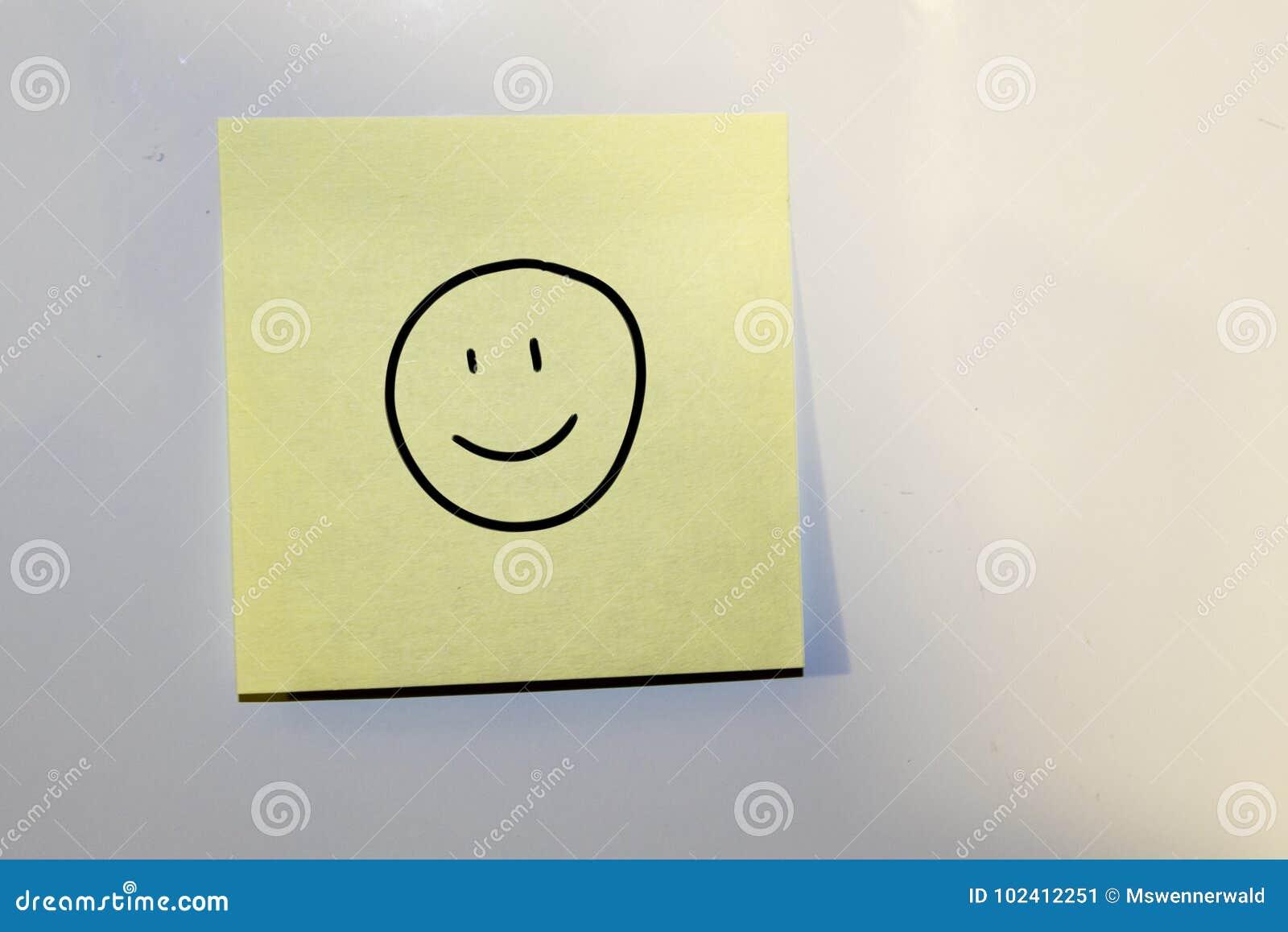 Haftnotiz mit einem glücklichen Gesicht gezeichnet