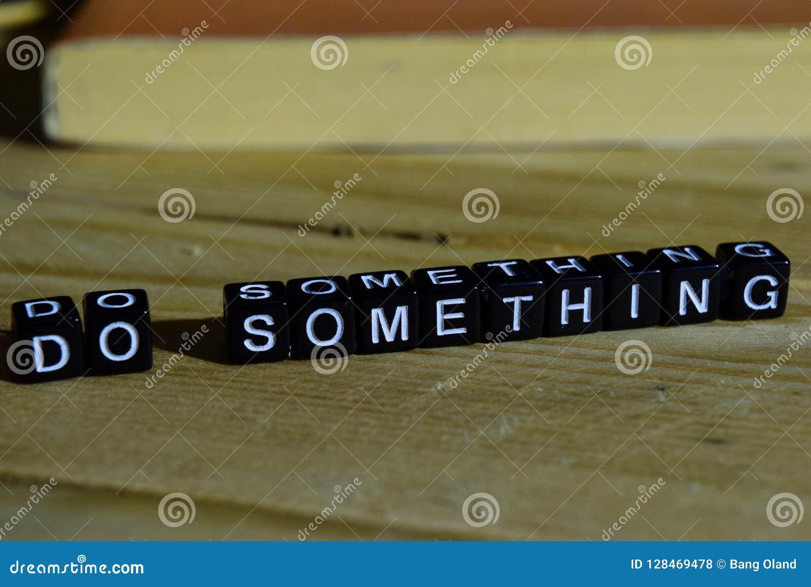 Haga algo en bloques de madera Concepto de la motivación y de la inspiración