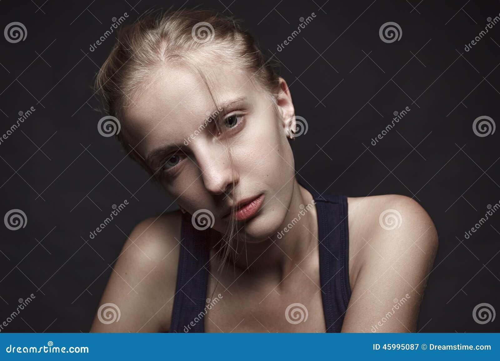 Haga frente al retrato de la mujer rubia joven sin maquillaje Backgro negro