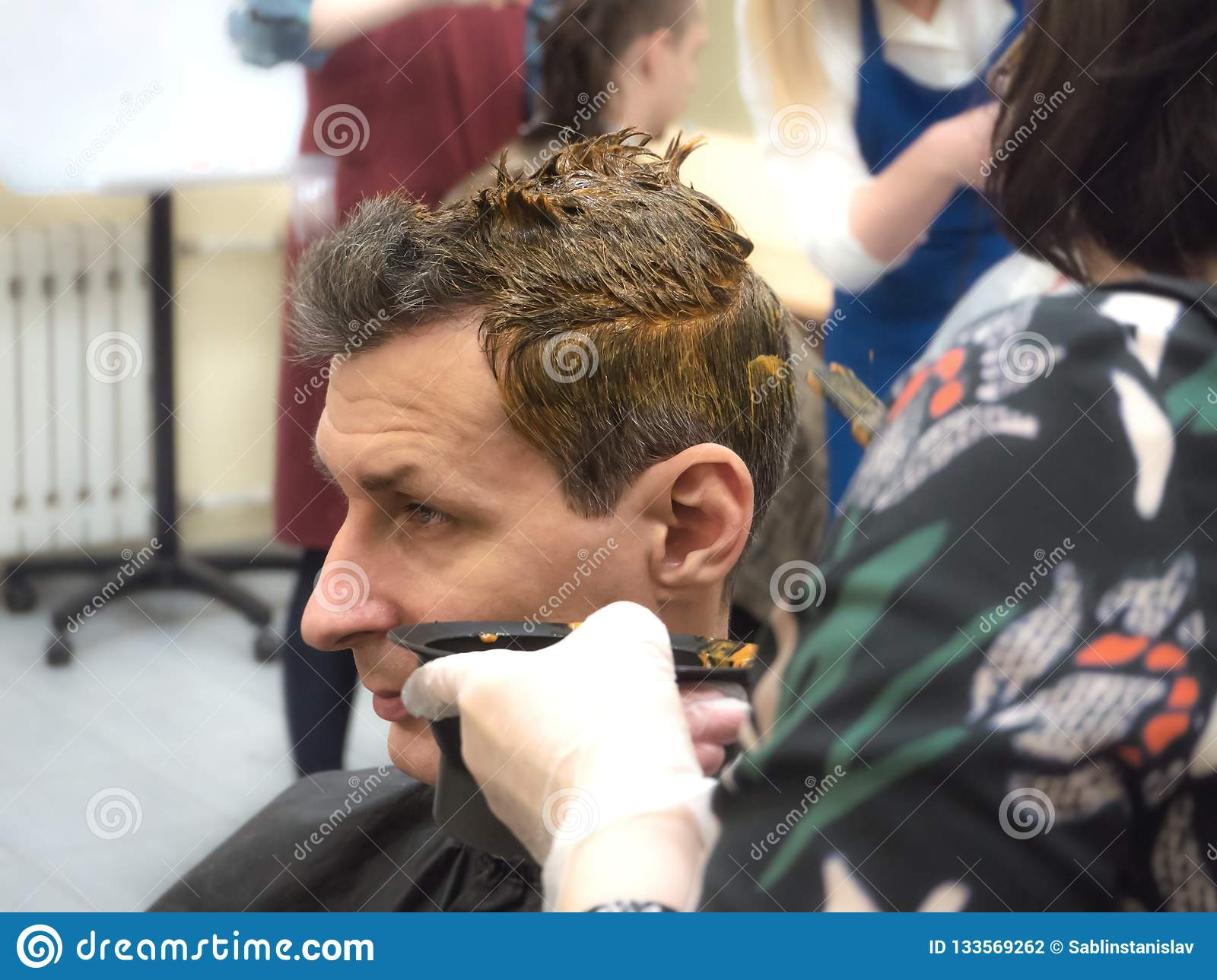 Hair coloring on a man in a beauty salon. Close up