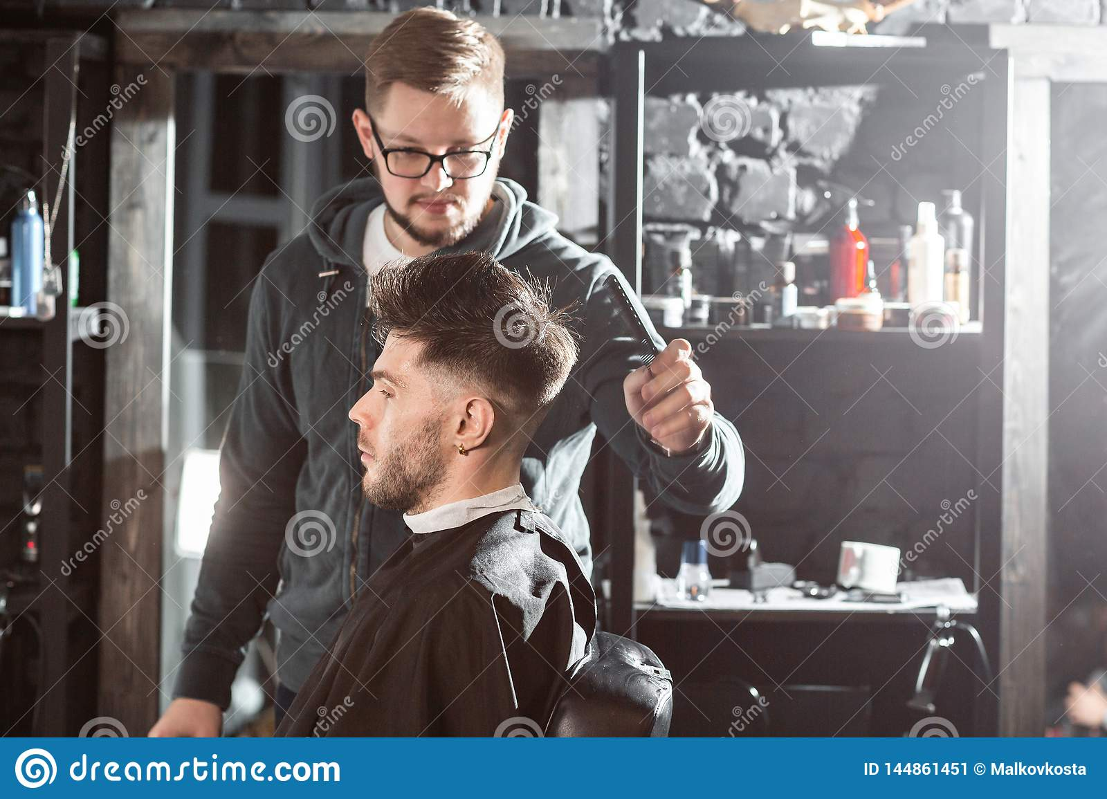 Hair cutting with metal scissors. Master cuts hair and beard of men in the barbershop, hairdresser makes hairstyle for a