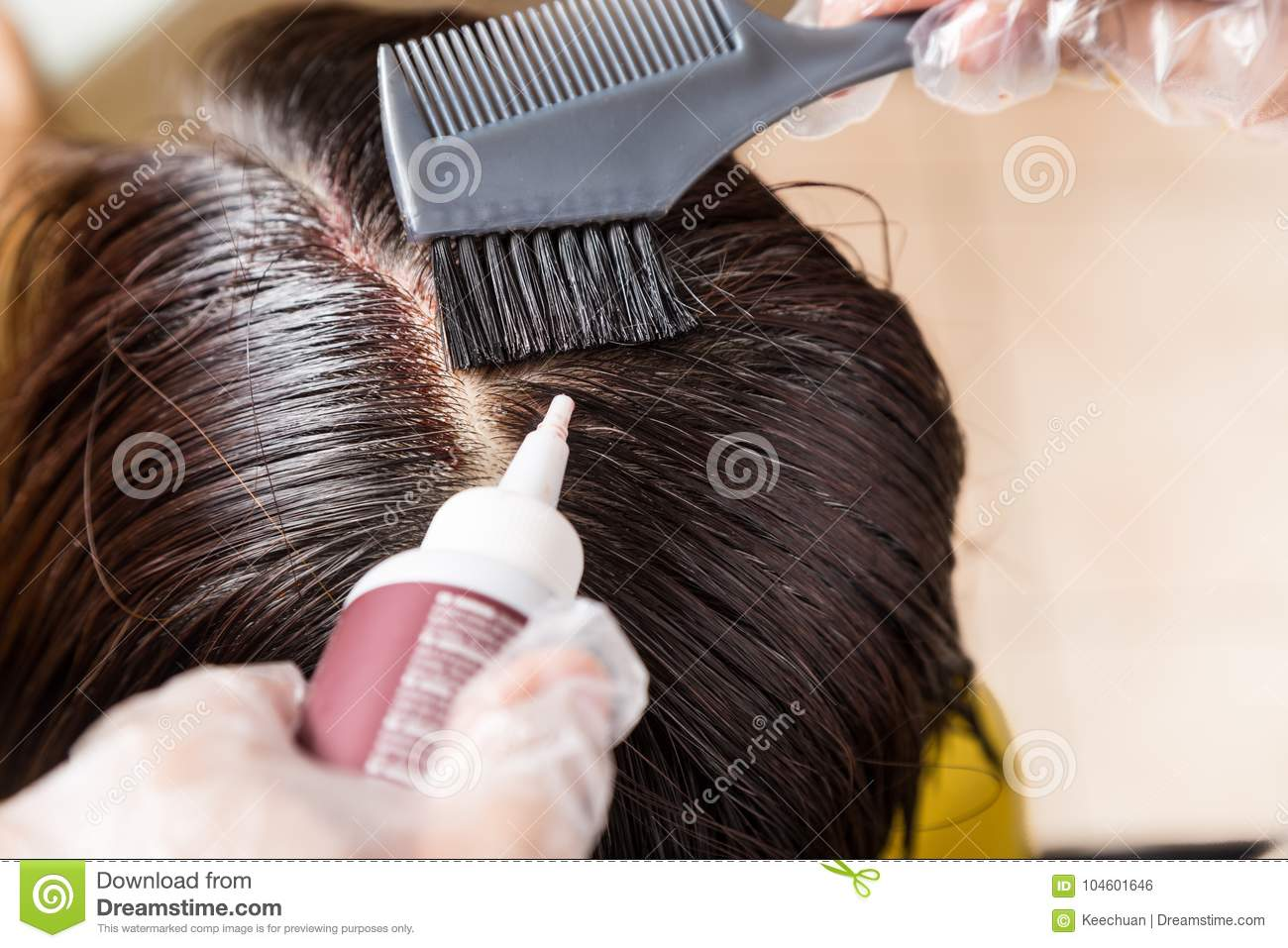 Hair Dresser Applying Chemical Hair Color Dye Onto Hair Roots Stock