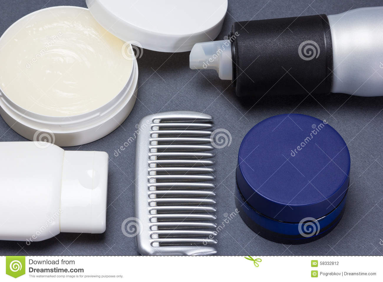 Hair styling products with comb on gray background