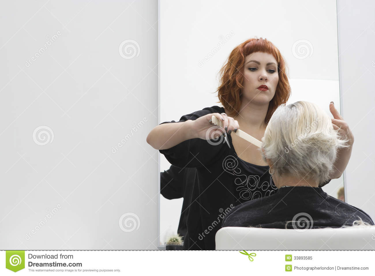 Hair stylist cutting senior woman 39 s hair royalty free for Salon seniors