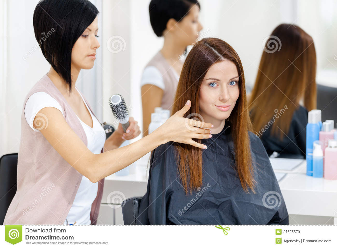 Hair stylist does hair style of woman in hairdressing salon