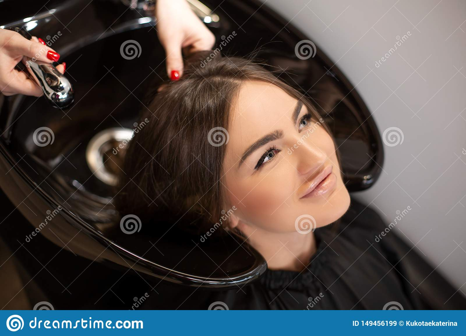 Haircut master washes hair of her client`s had