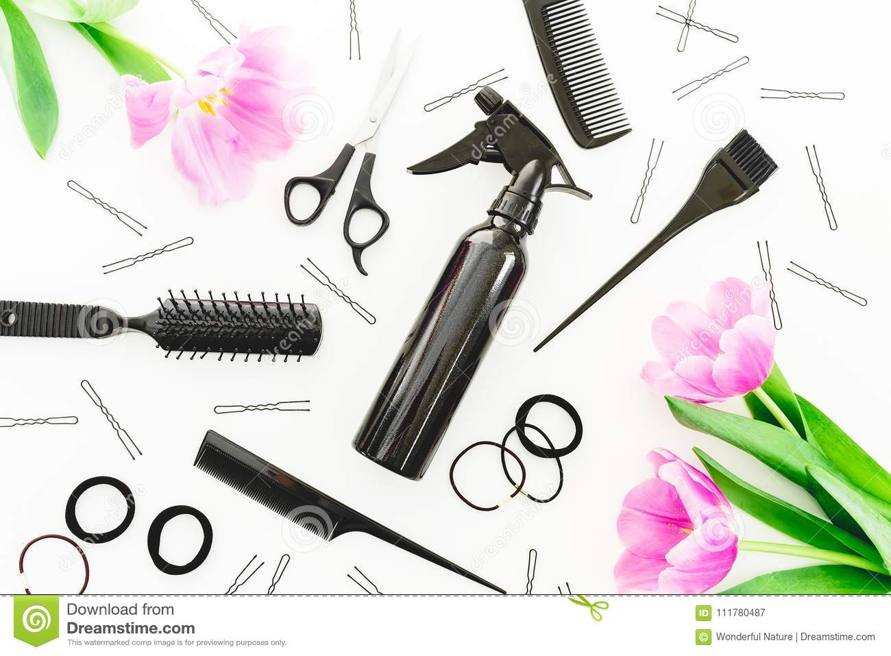 Hairdresser concept with spray, scissors, combs, barrette and tulips flowers on white background. Beauty concept. Flat lay, top vi