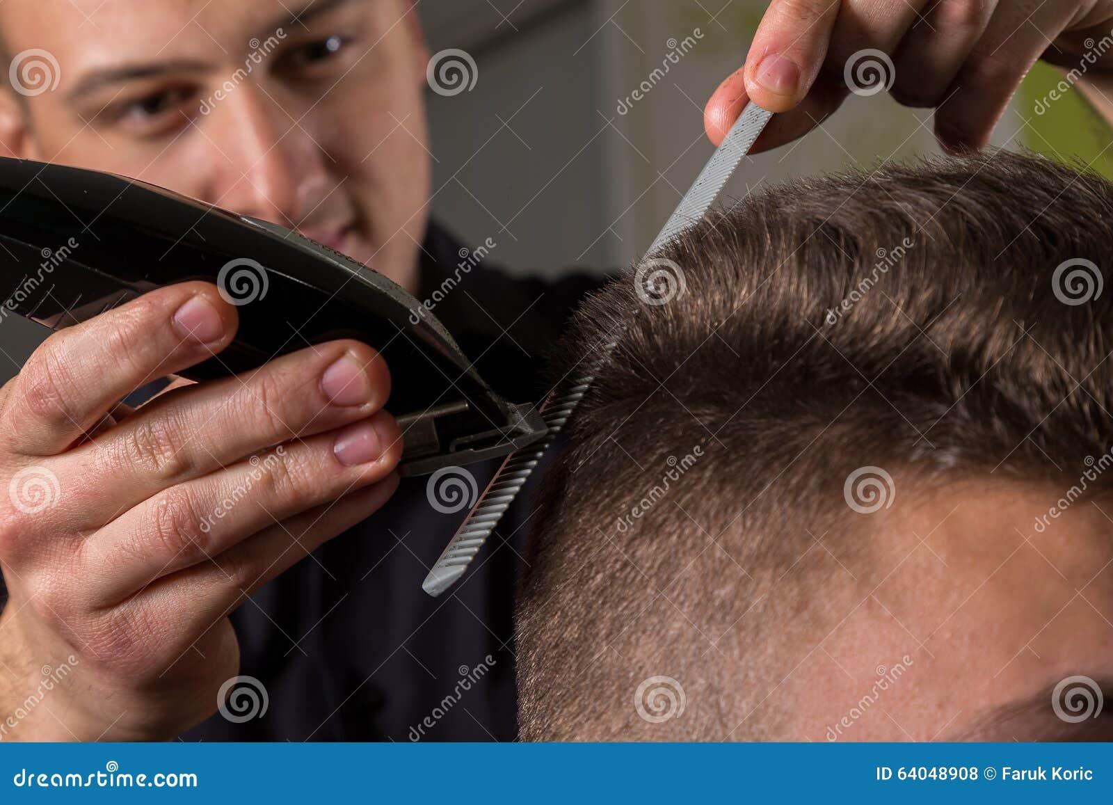 Hairdresser cutting clients hair with an electric hair clipper