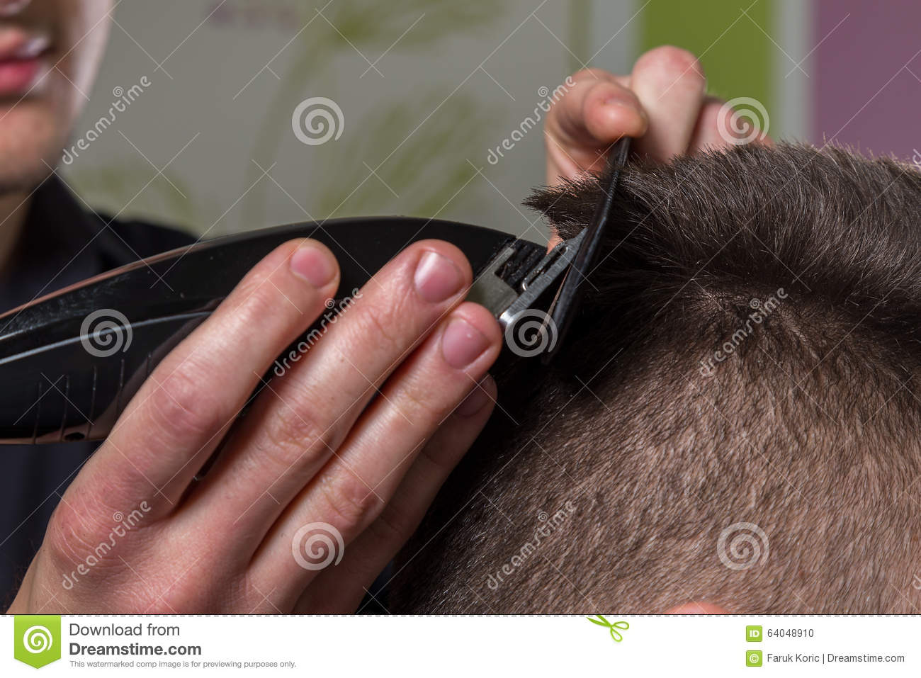 Hairdresser cutting clients hair with an electric hair clipper