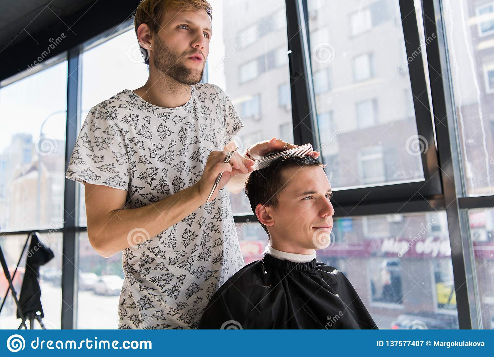 Hairdresser does hair with comb of handsome satisfied client in professional hairdressing salon