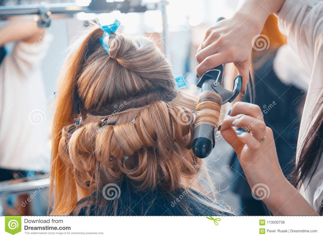 The Hairdresser Does Hair Extensions To A Young Girl Stock Photo