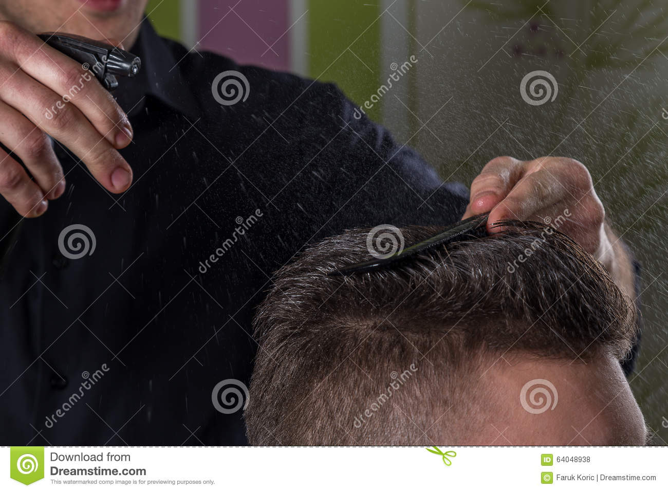 Hairdresser does hair with water and comb of client in professional hairdressing salon
