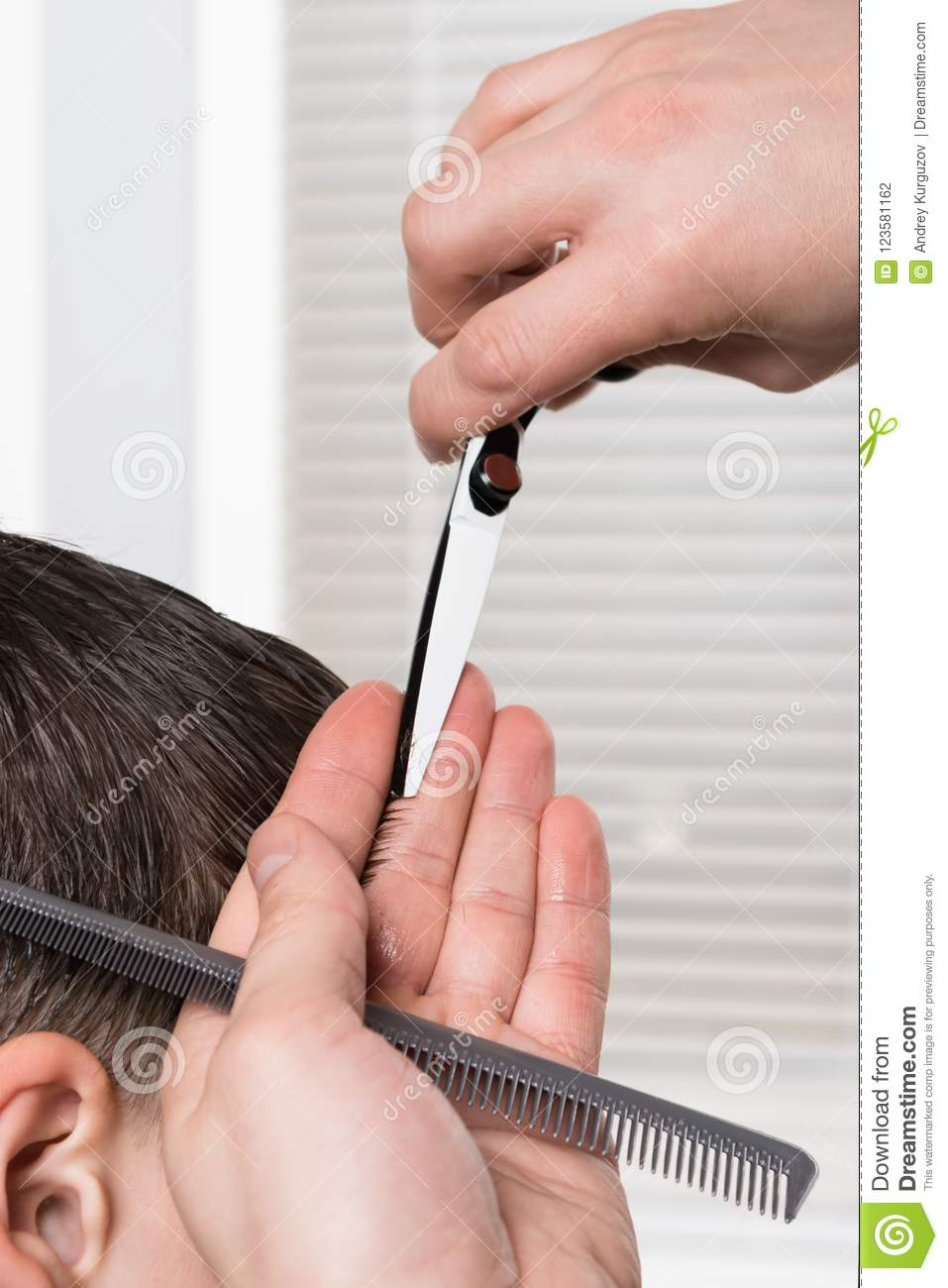 Hairdresser Does A Haircut With A Scissors Boy Close Up Stock Photo