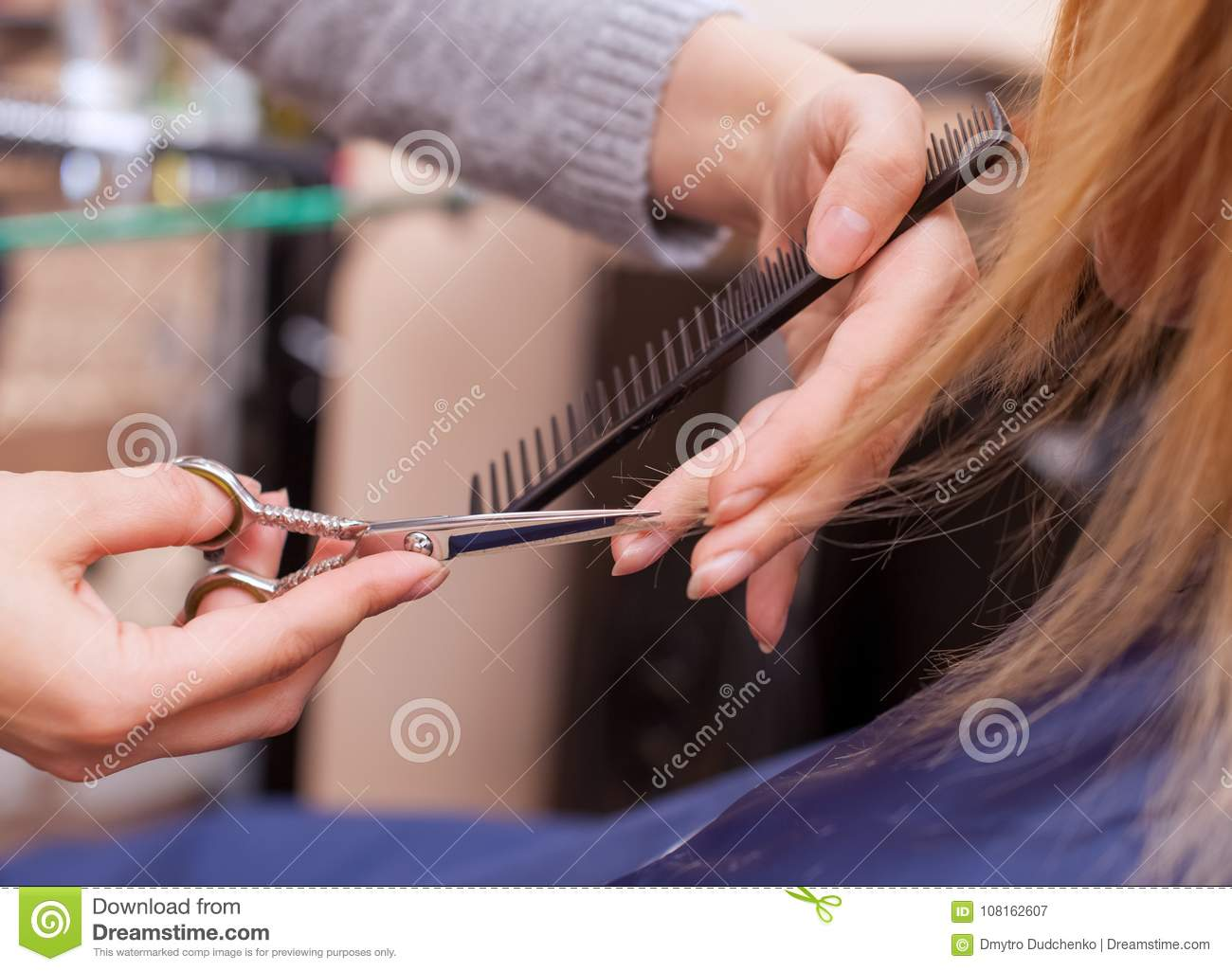 The Hairdresser Does A Haircut With Scissors Of Hair To A Young Girl