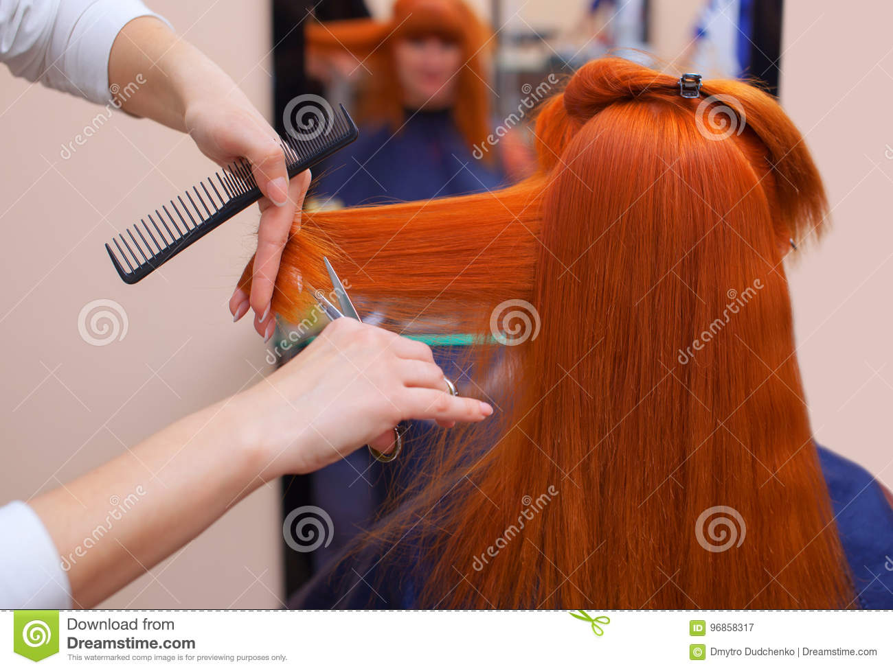 The Hairdresser Does A Haircut With Scissors Of Hair To A Young With