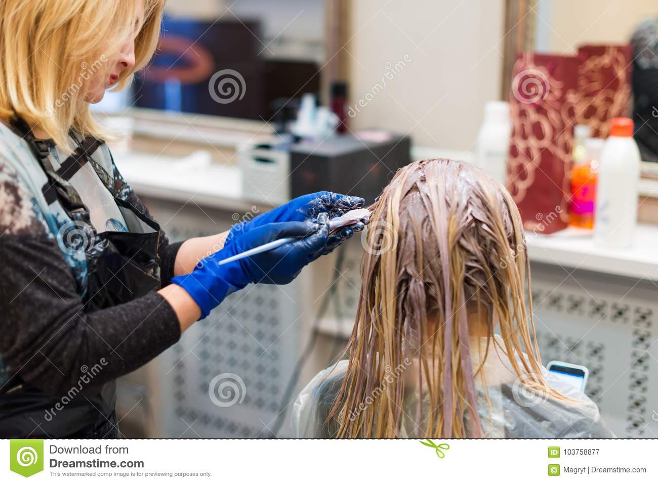 Hairdresser is dying female hair. Hands in glives with brush, coloring in hair salon.