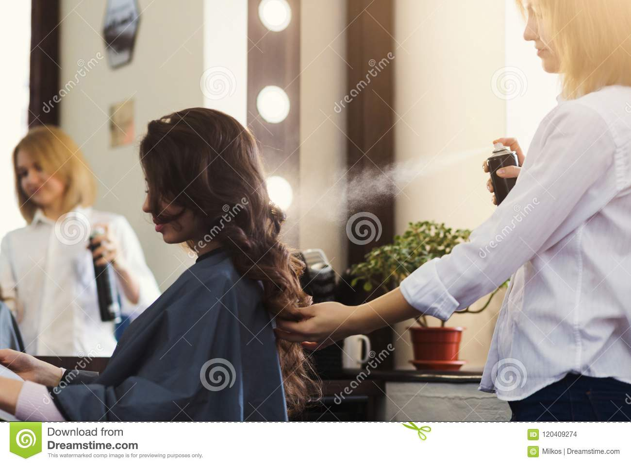 Hairdresser making curly hairstyle at beauty salon