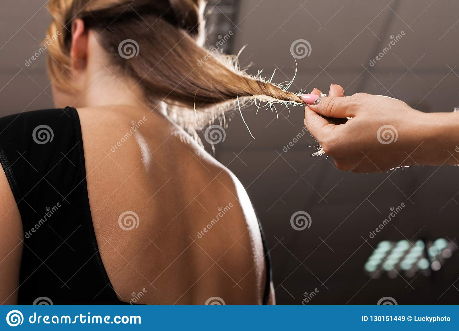 Hairdresser holding hair of a model with split ends