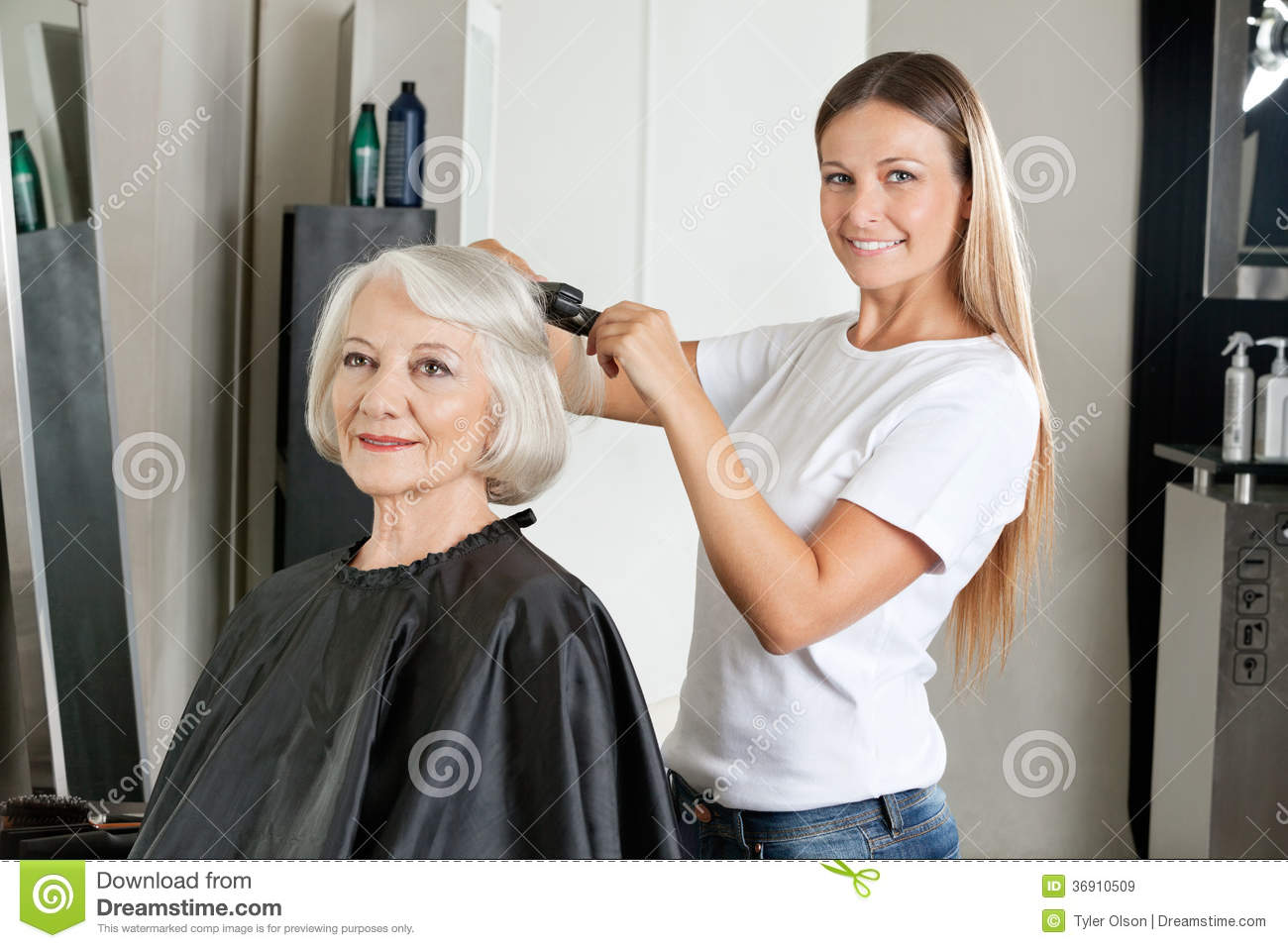 Hairdresser ironing woman 39 s hair royalty free stock images for Salon seniors