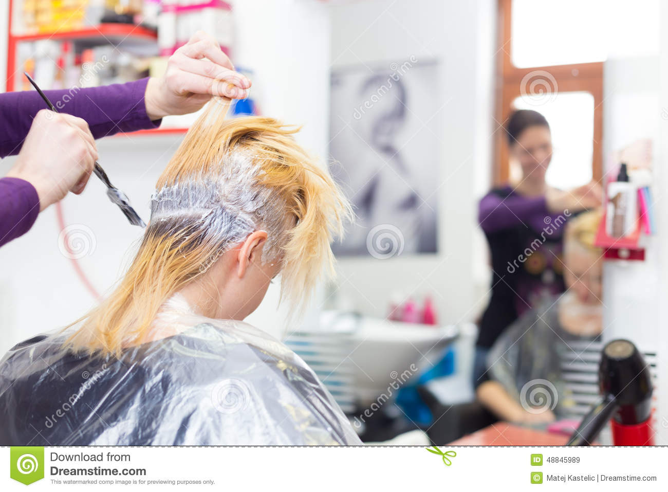 hairdresser salon woman during hair dye stock photo