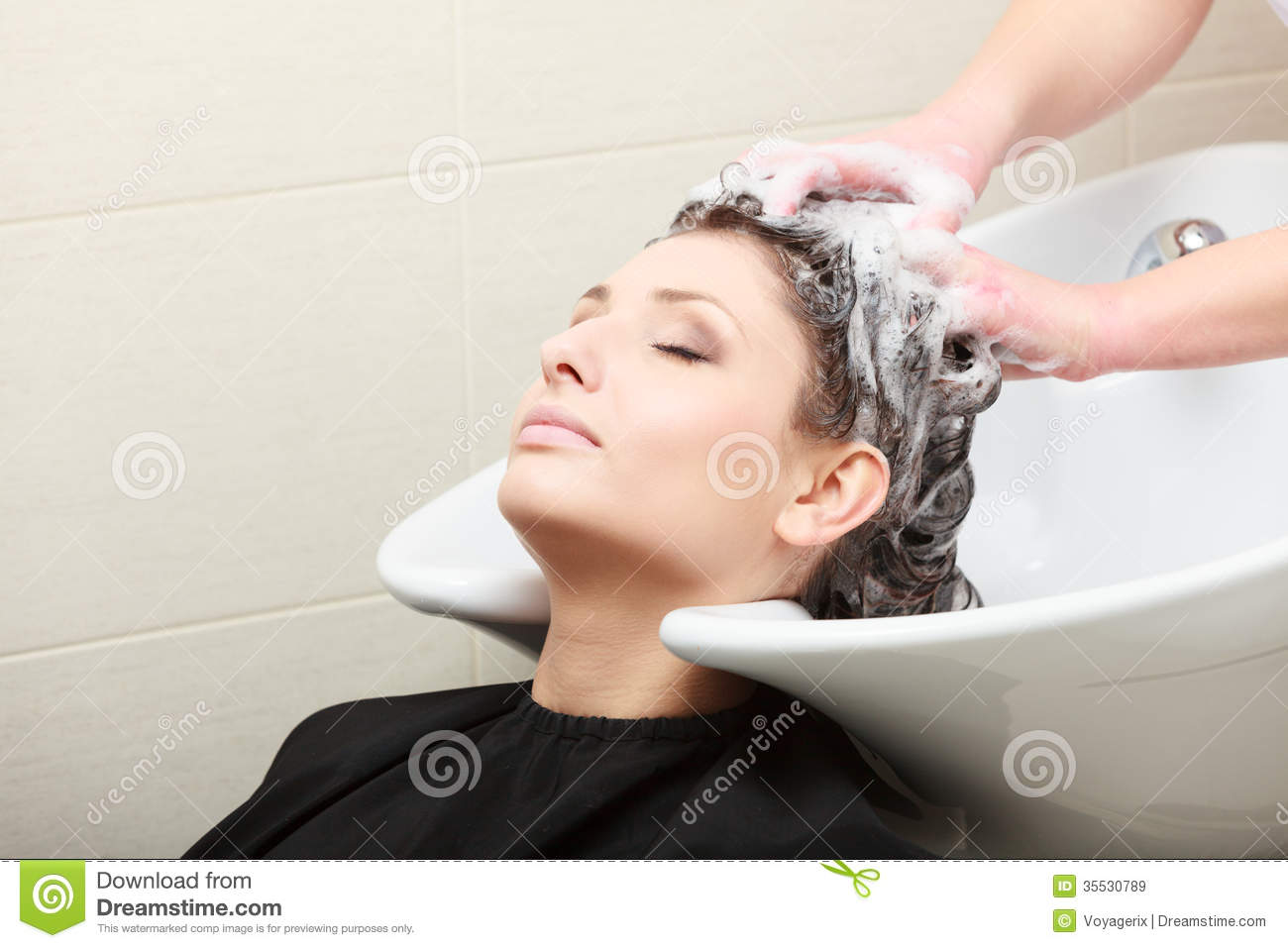 Young women relaxing in hairdressing beauty salon. Hairstylist washing ...