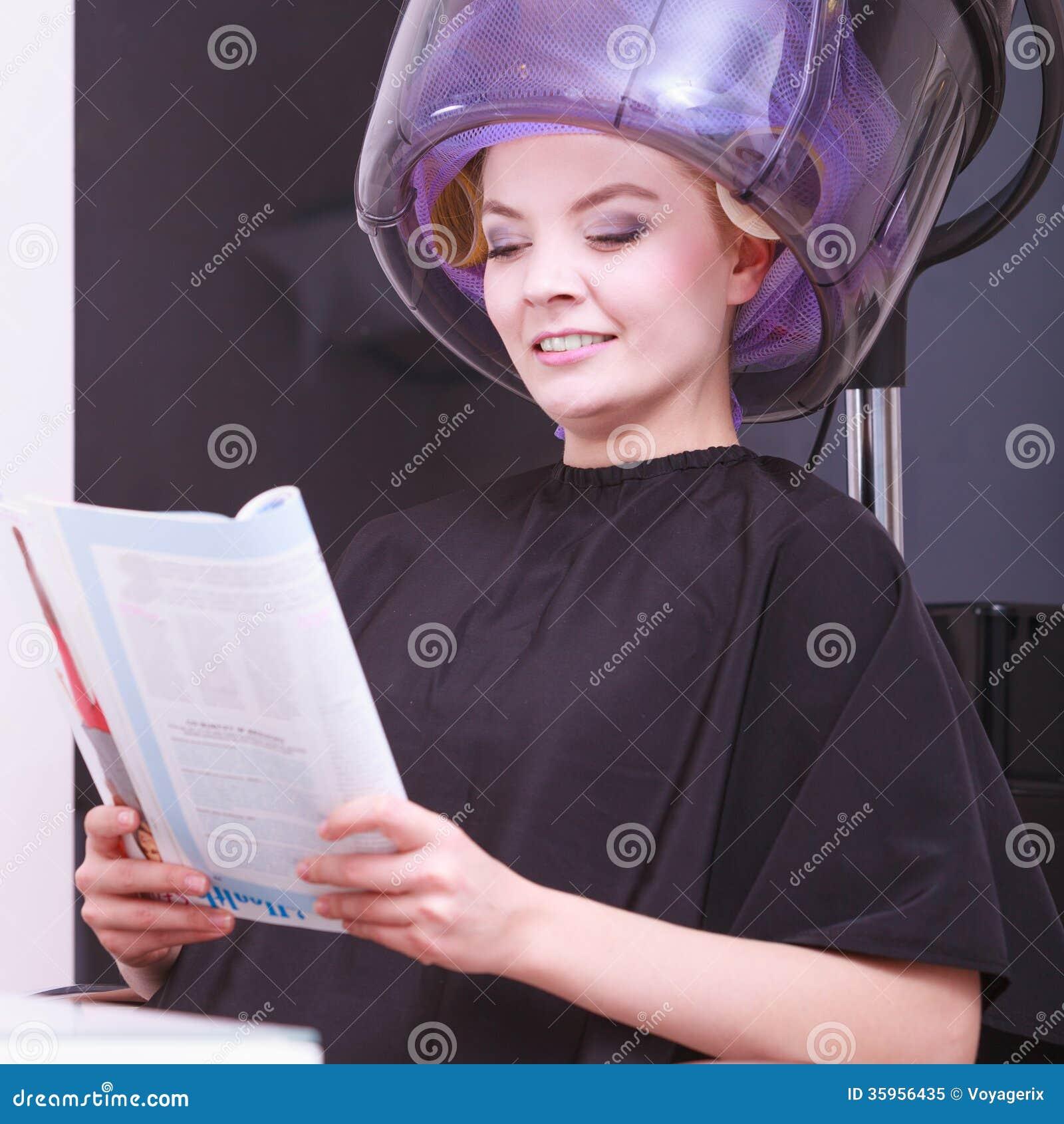 Hairdryer relajante de la revista de la lectura de la muchacha del peluquero en salón de belleza del pelo