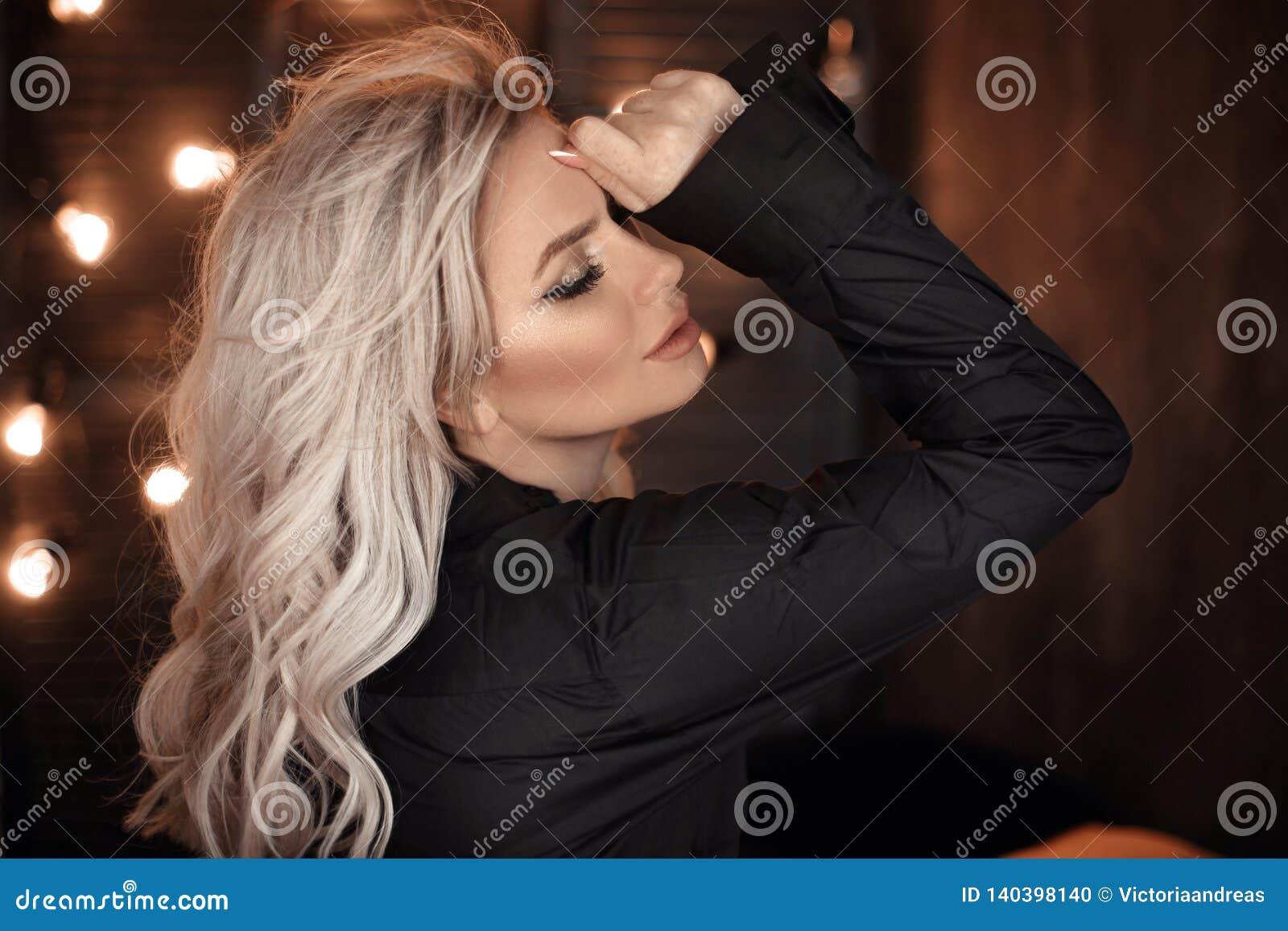 Hairstyle Retrato louro bonito da mulher que levanta na camisa preta Modelo louro elegante da menina sobre o fundo escuro das luz