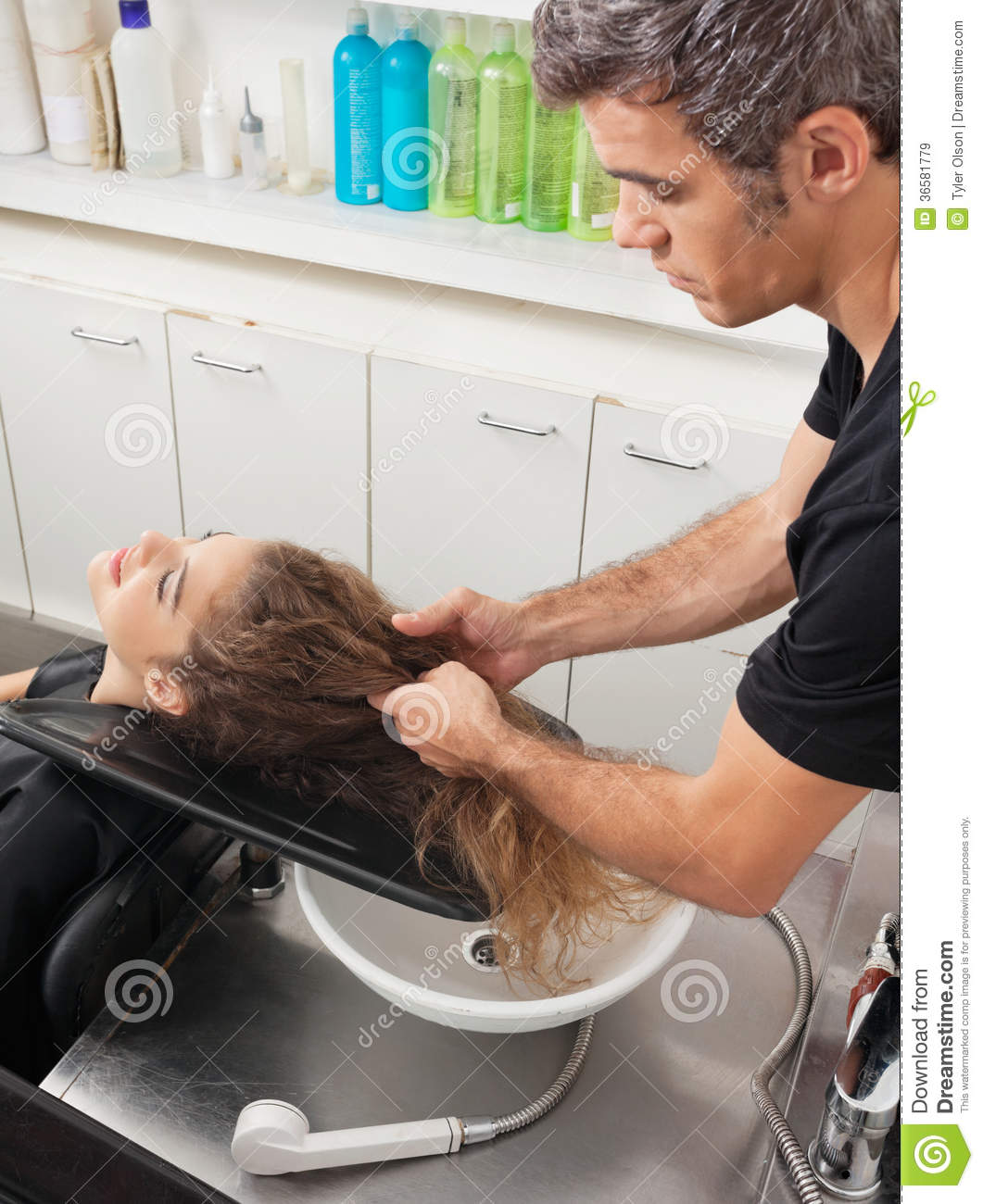 Hairstylist with client preparing for hair wash royalty for Wash hair salon