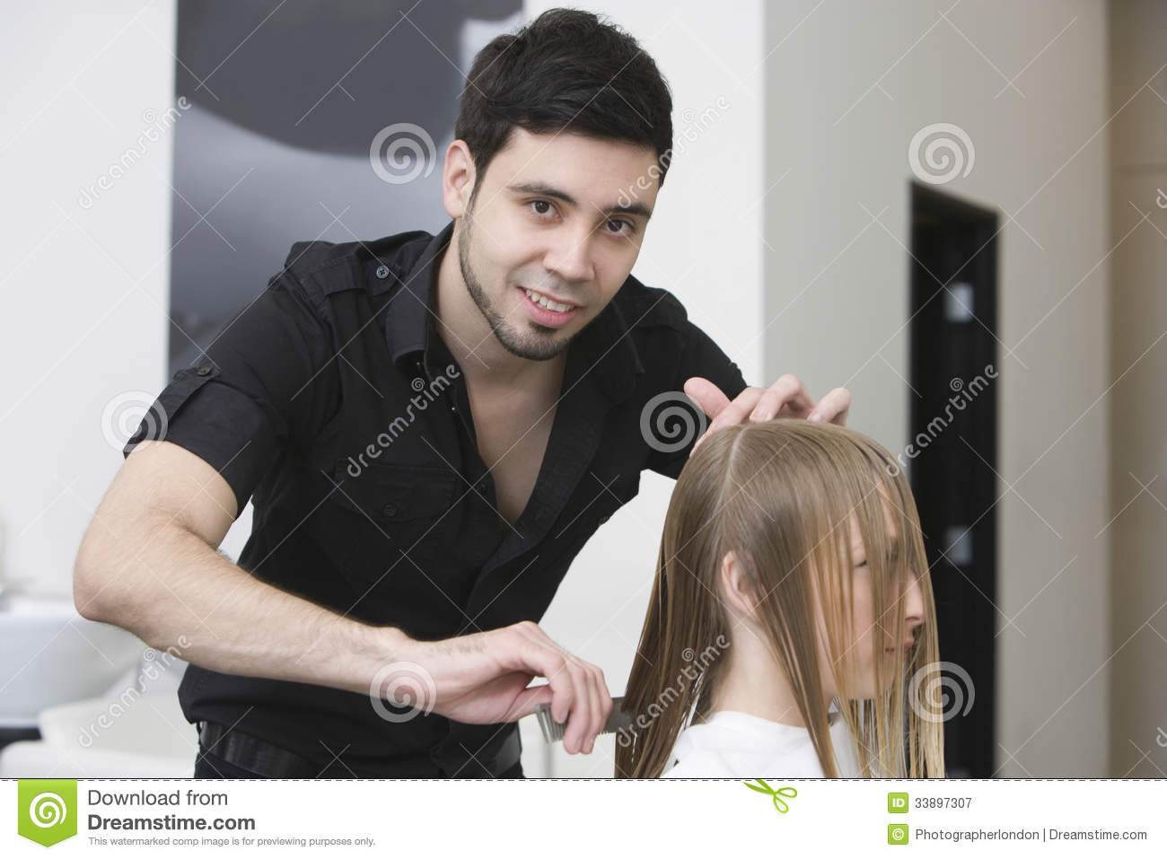Hairstylist Combing Client's Hair At Salon Stock Image ...