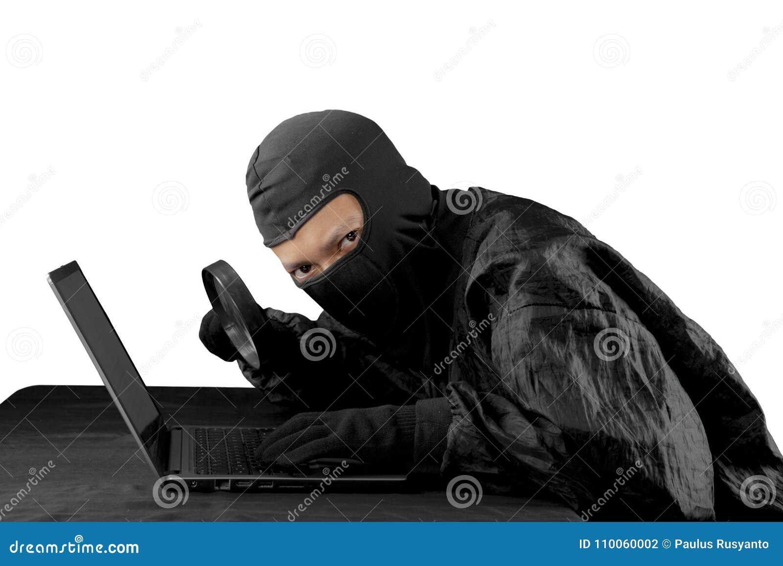 Hakker die vergrootglas op een laptop computer met behulp van