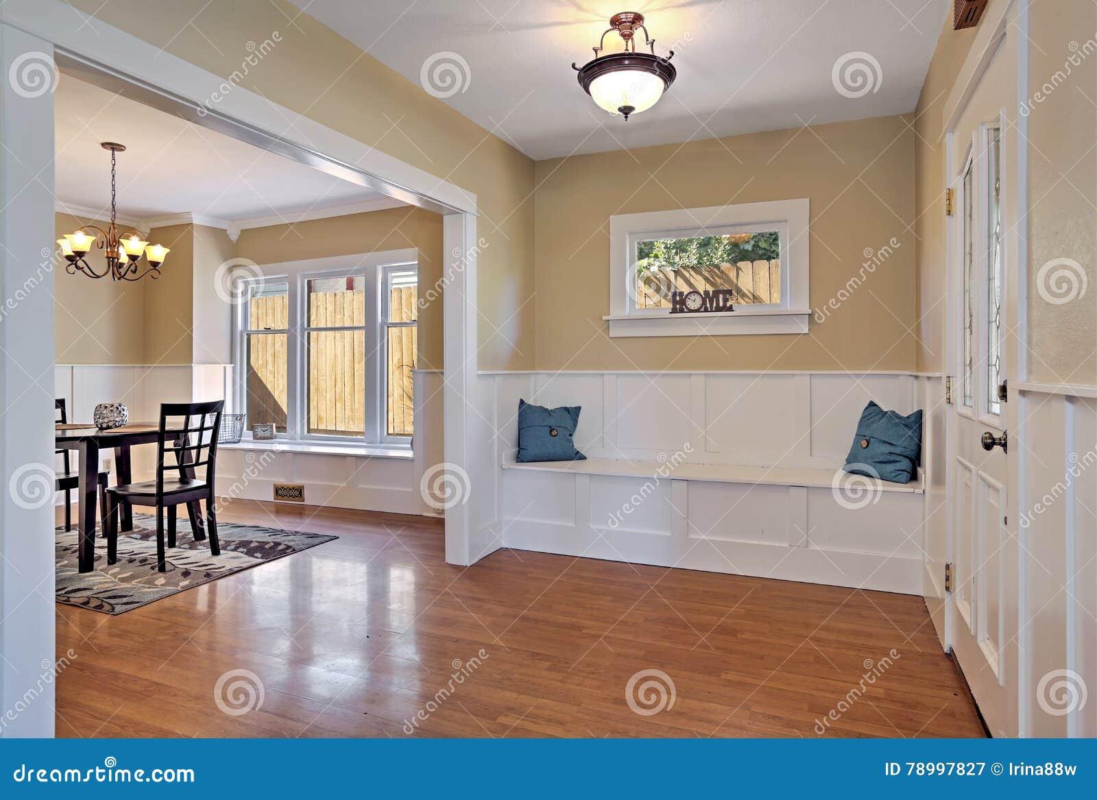 Hal met hout met panelen beklede muren en comfortabele zetel stock