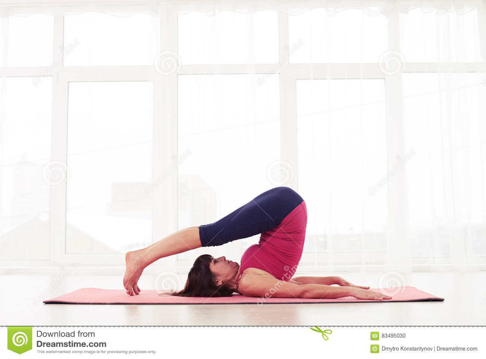 Halasana di yoga di pratiche di yogini di misura sportiva o posa maturo dell aratro