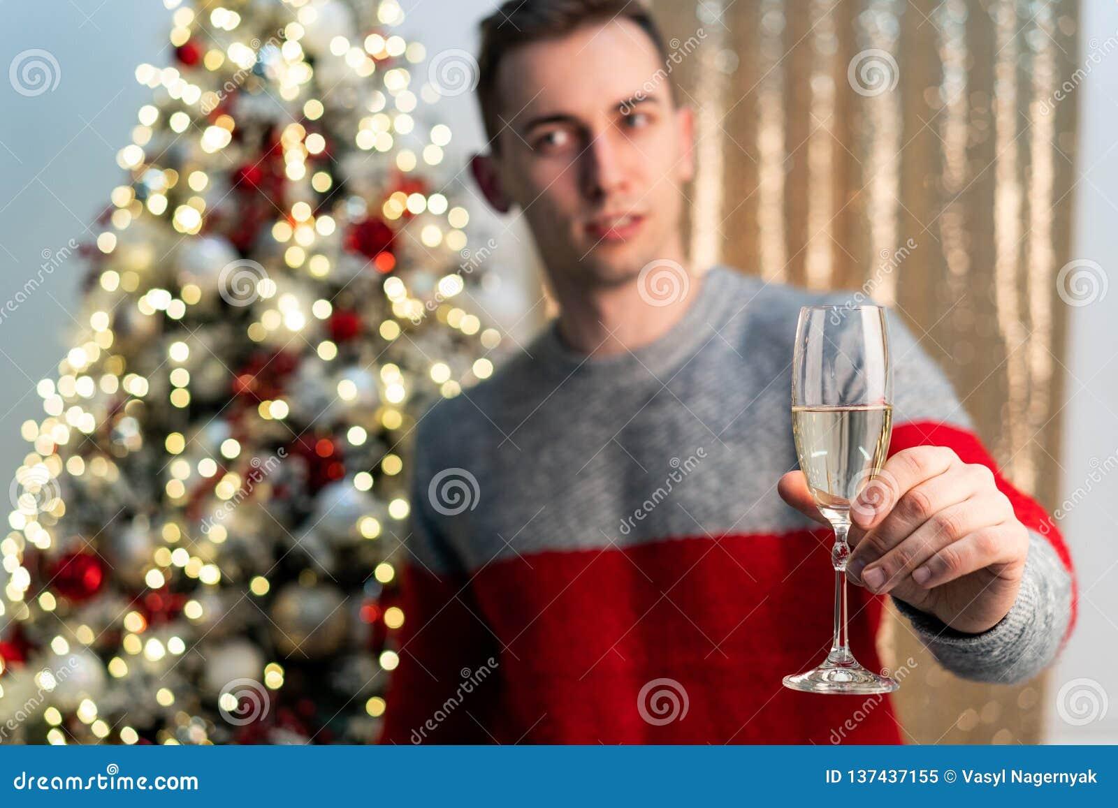 Halbes lengh Porträt des hübschen Kerls mit Champagner röstend zu werdenem Jahr