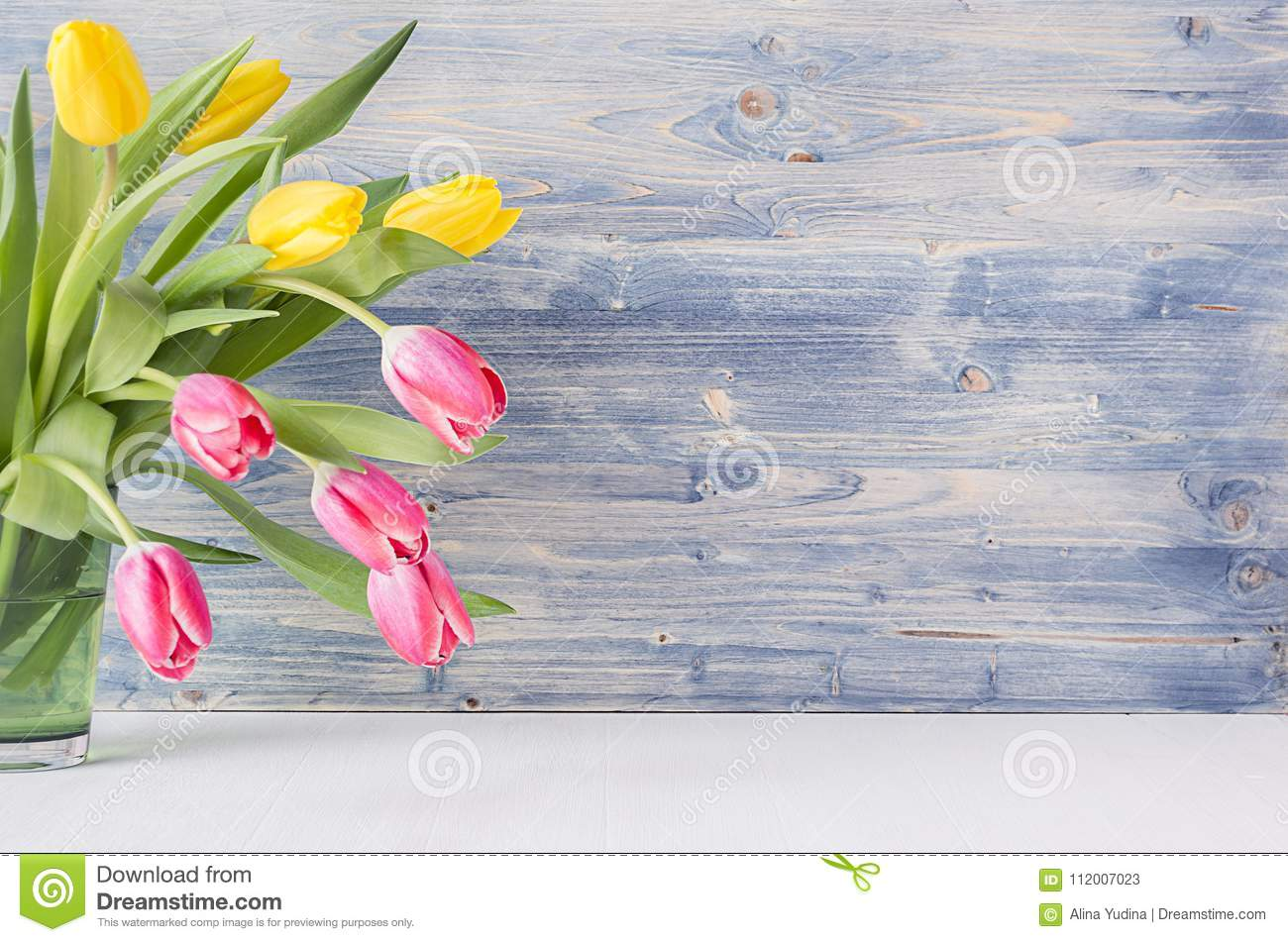 Half bouquet red and yellow tulips in green glass vase on blue shabby wooden background with copy space. Spring easter home decor.