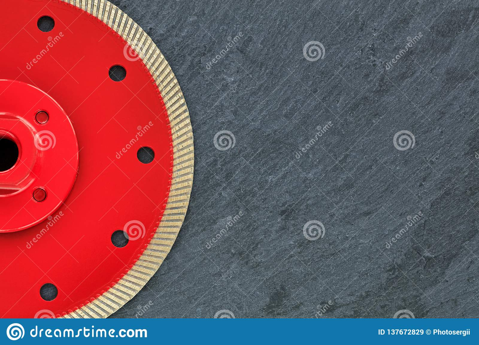 Half of the diamond cutting wheel is red with a threaded nut on a background of gray granite