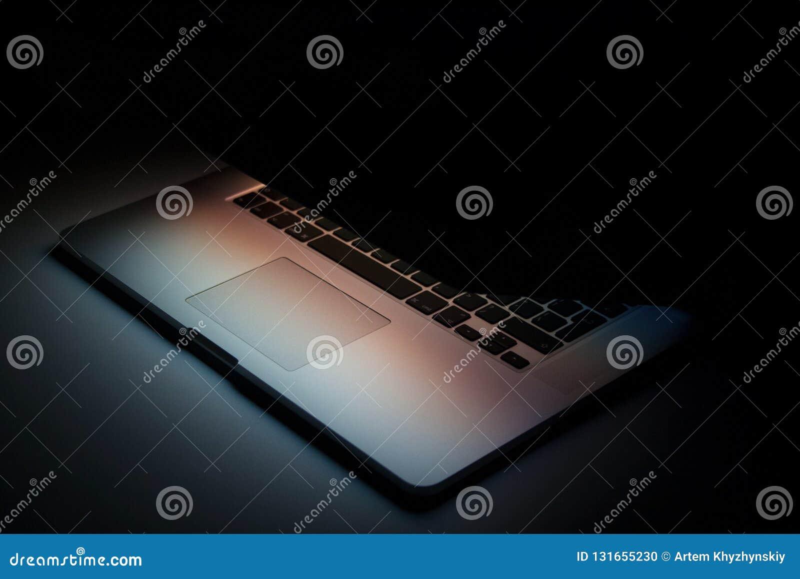 Half gesloten zilveren laptop met het schermlicht op zwarte achtergrond