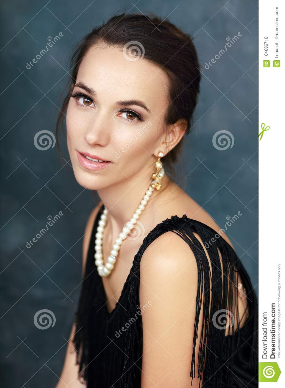 3568f02632d Half length portrait of beautiful young elegant woman with pearls in black  dress posing next to color background