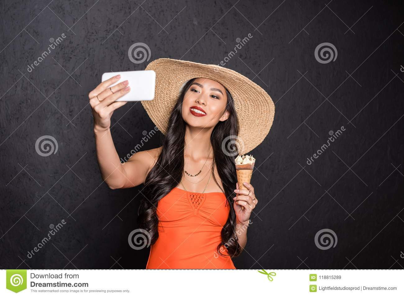 f2f7bcbd8e Half-length shot of a beautiful asian woman in beach attire holding an ice- cream and taking selfie with smartphone