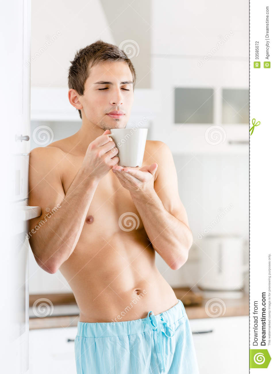 Half-naked young man with cup of coffee at kitchen