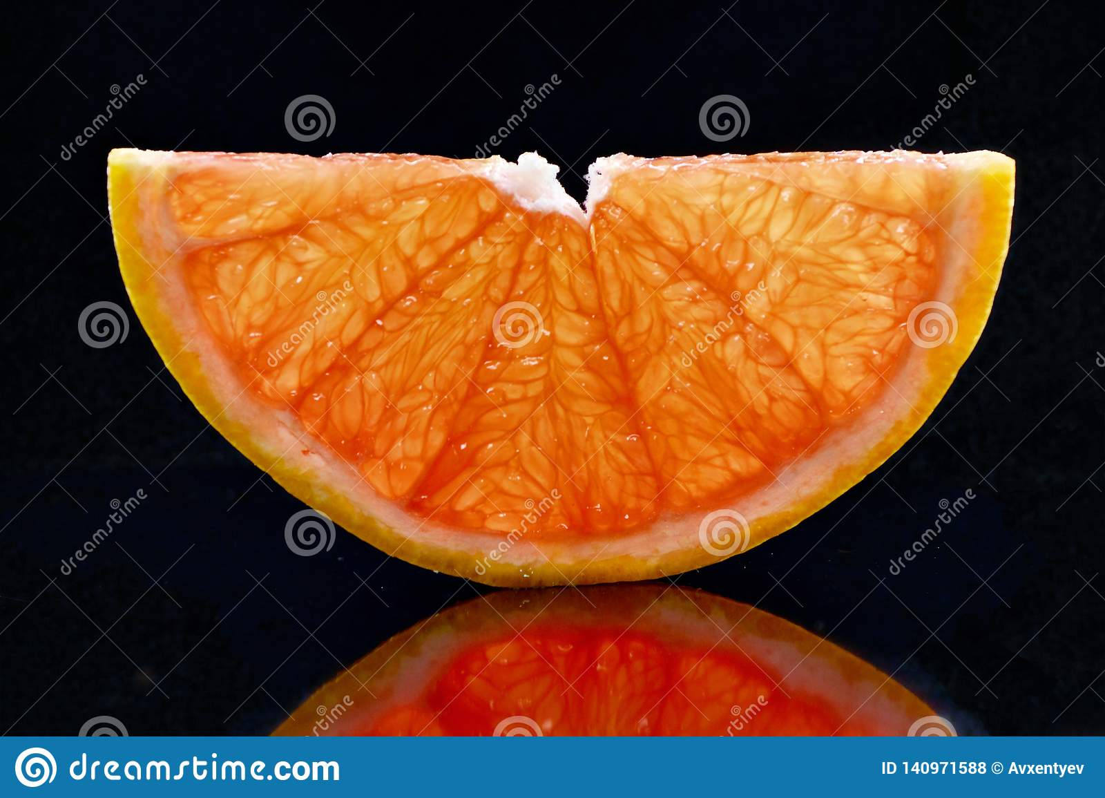 Half transparent slice of grapefruit on a black background.