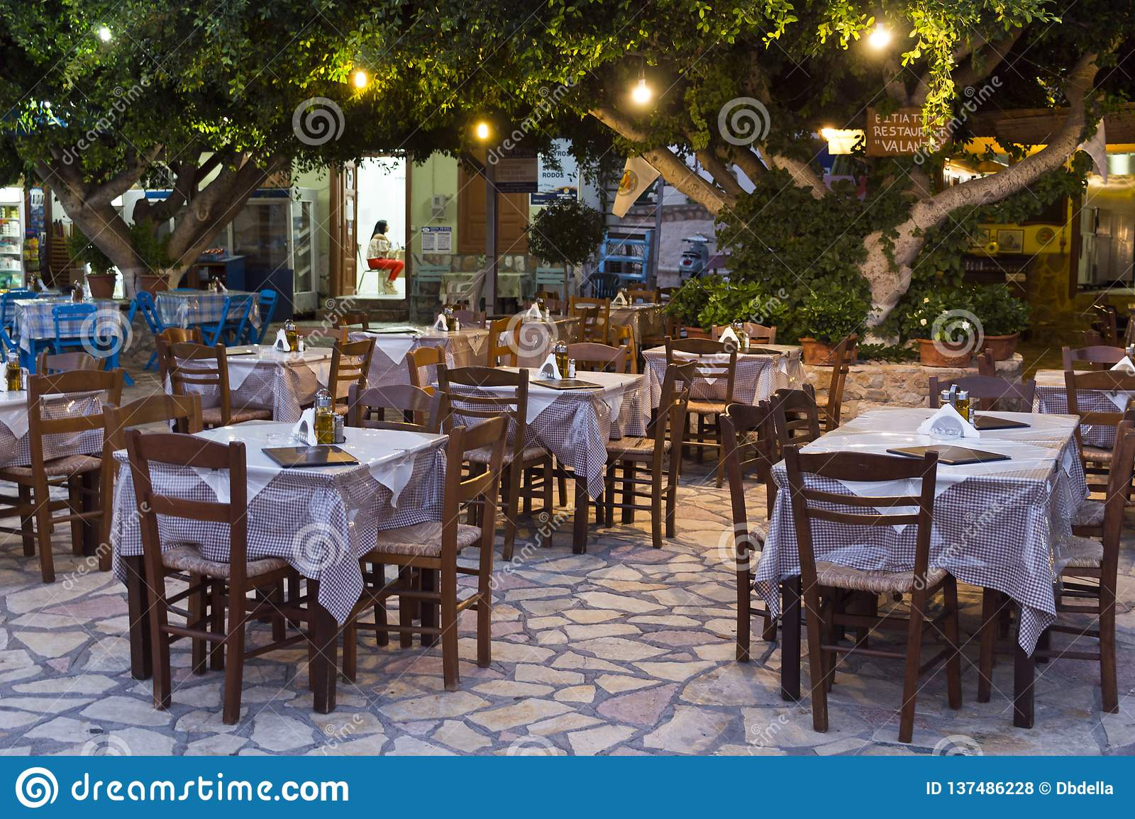 Halki, Emborios village - Traditional greek restaurants, tables and chairs waiting for customers in the night. Dodecanese Islands,
