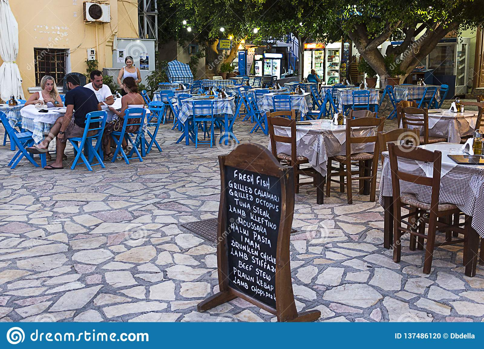 Halki, Emborios village - Traditional greek tavern restaurant, tables and chairs.Dodecanese Islands, Greece