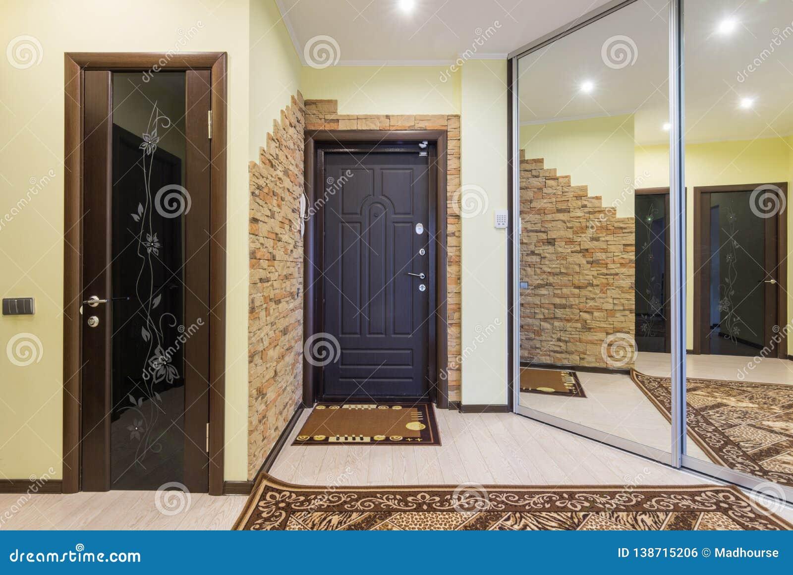 Hall de entrada espacioso en el apartamento con el guardarropa incorporado y los espejos