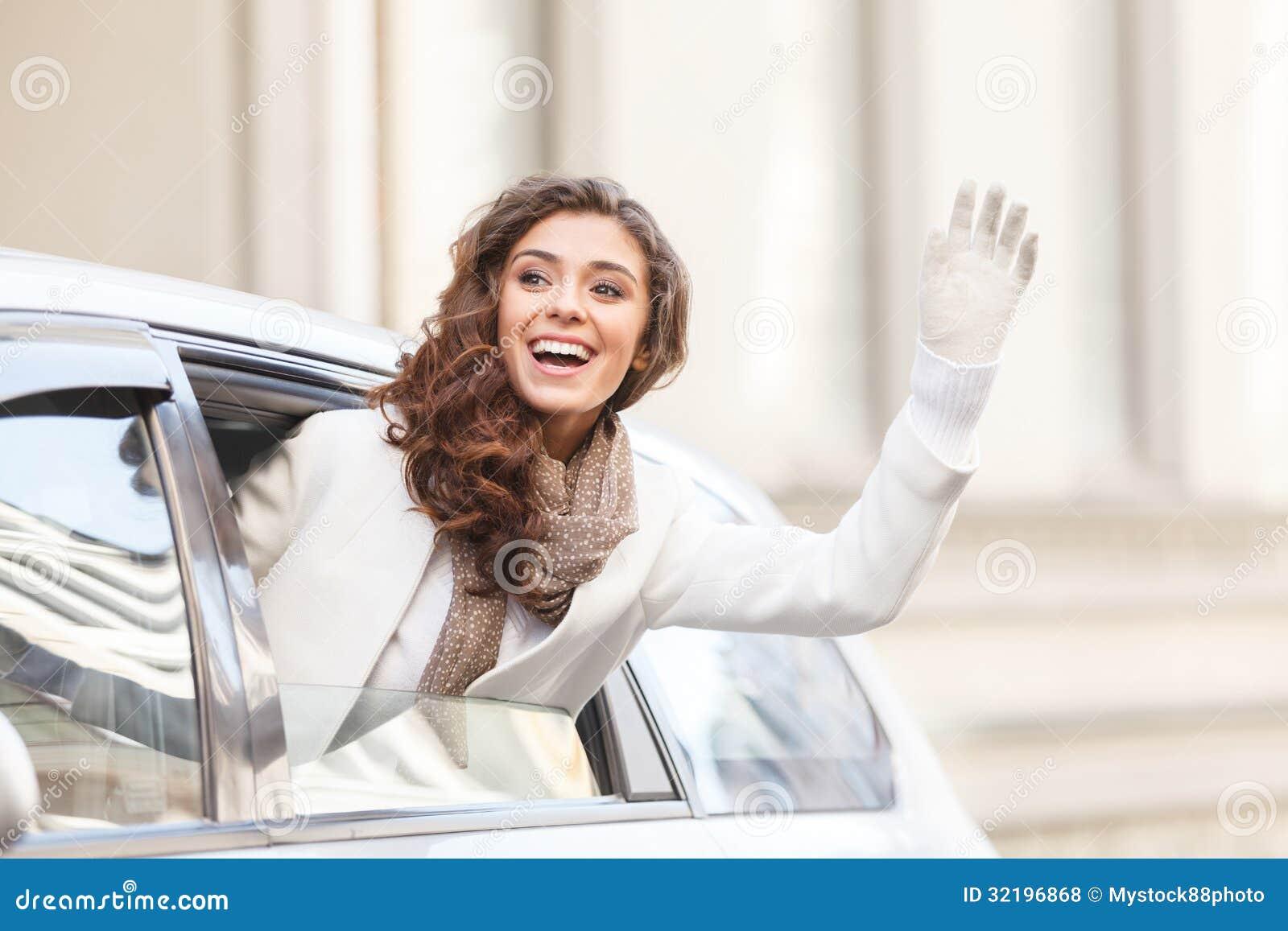 Hallo! Schöne junge Frau, die heraus von einem Guten Tag sagenden Auto schaut