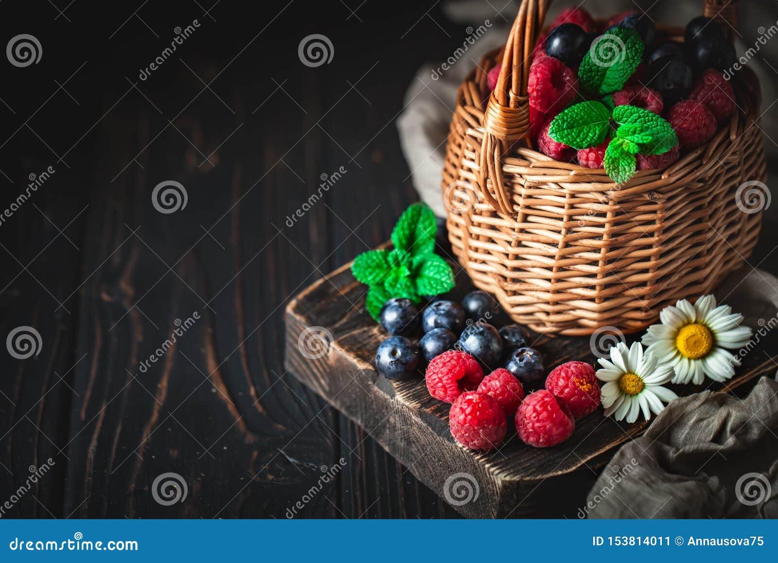 Hallon och bl?b?r i en korg med kamomill och sidor p? en m?rk bakgrund Sommar och sunt matbegrepp