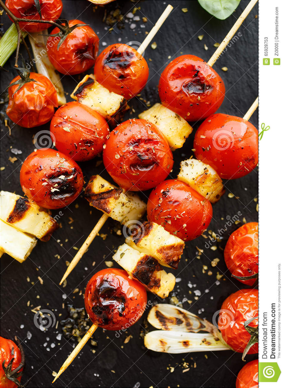 Halloumi cheese and cherry tomato skewers on stone black background