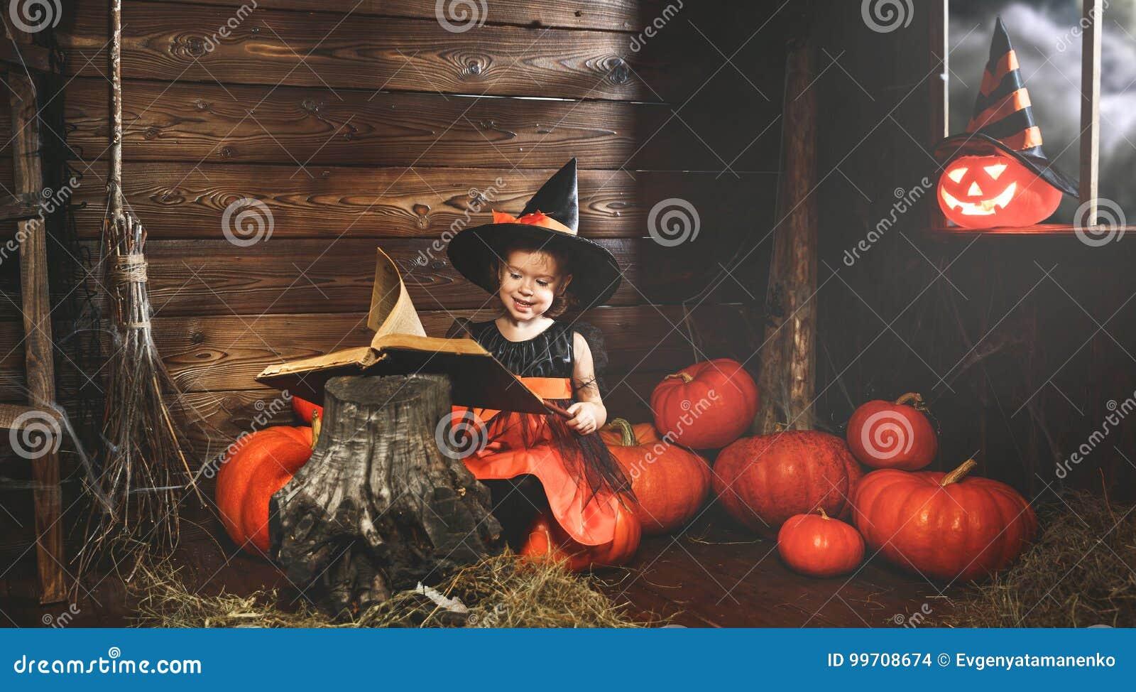 Halloween ребенок ведьмы колдует с книгой произношений по буквам, волшебной палочки и тыкв