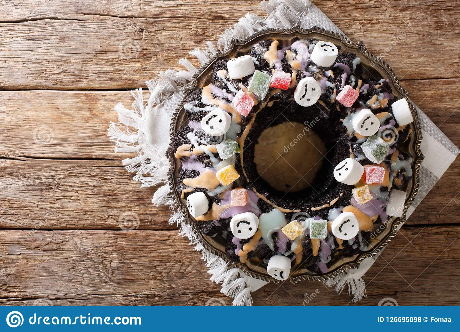 halloween black bundt cake decorated with candied fruits, marshm